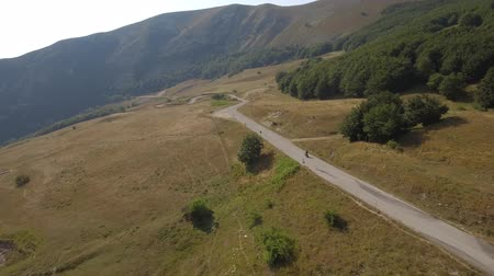 enrolamento : Aerial view of a man driving a motorbike on a mountain road. Drone video of motorcycle on a road winding through the countryside. Transport and travel concepts