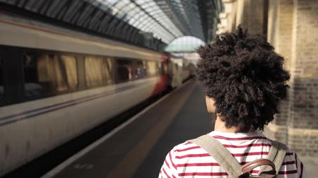 портретный : Man walking to the train at station, slow motion - Curly mixed race man on a trip, seen from behind - Travel and lifestyle concepts Стоковые видеозаписи