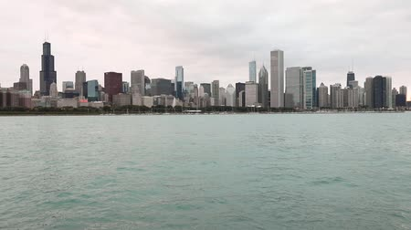 Chicago skyline and Lake Michigan on a cloudy day. Chicago downtown with tall skyscrapers on background, water in foreground. Steady view. Travel and architecture concepts. 動画素材
