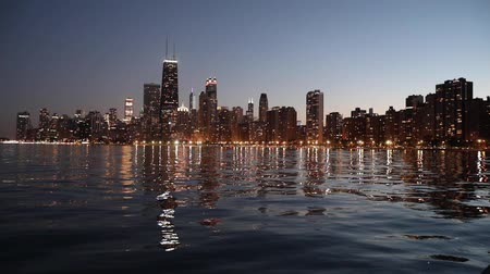 Chicago skyline and Lake Michigan at dusk. Chicago downtown with illuminated skyscrapers at night on background, water in foreground. Steady view. Travel and architecture concepts.