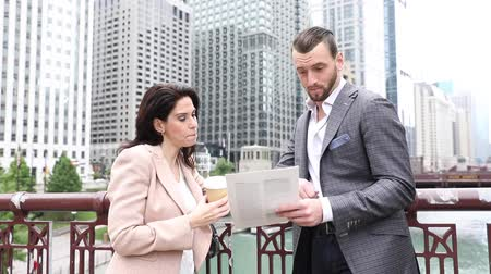 Business people meeting and talking in Chicago. Man and woman, wearing smart casual clothes, looking each other and smiling. Downtown skyscrapers on background Wideo