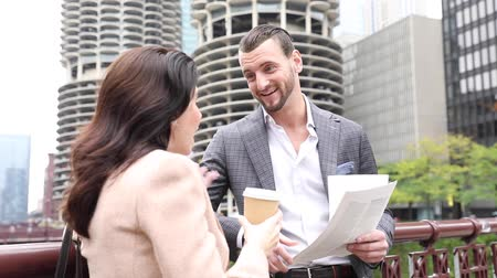 Business people meeting and talking in Chicago. Man and woman, wearing smart casual clothes, looking each other and smiling. Downtown skyscrapers on background 動画素材