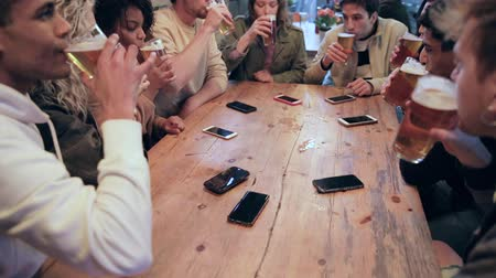 make friends : Group of friends enjoying a beer at pub in London, toasting and laughing - Multiracial group of people having fun together and drinking a pint of beer - Lifestyle and drinks