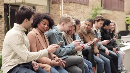 Multiracial group of friends with smartphones in the city - Big group of people sitting together and looking at their phones - Social media concept and addiction, millennials lifestyle in London