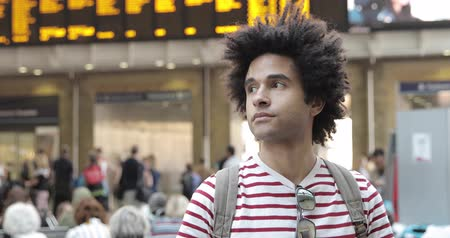 Mixed race man at train station portrait  - Afro caribbean man looking around while waiting for the train - Travel and lifestyle concepts 動画素材