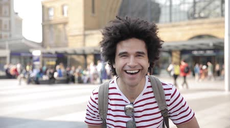 Man laughing in slow motion in front of busy train station - Portrait of mixed race man in London enjoying his trip and having fun