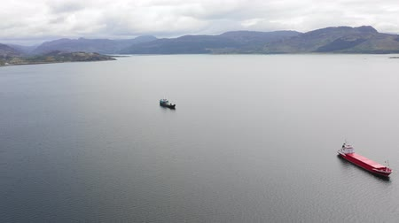 Aerial view of nautical vessel in Scotland - Boat on a Scottish loch, a lake connected to the sea, with mussel farms on background - Transportation and nature concepts 動画素材
