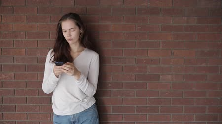 Happy woman typing on the phone and smiling - Beautiful young woman leaning against brick wall and chatting, slow motion video - Lifestyle and technology concepts 動画素材