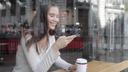 Young woman in a cafe enjoying a coffee and using a smartphone - Beautiful brunette sitting behind a window in a cafe bar in London, looking away from camera - Lifestyle and food drink concepts