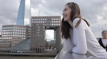Young beautiful woman portrait in the city - Smiling happy woman with London landmarks and Thames river on background - Lifestyle and relax concepts, slow motion