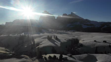 baita : Aerial view of mountains with snow at sunrise - Backlight panoramic video of Dolomites in winter with snow on the valley - Nature and travel concepts