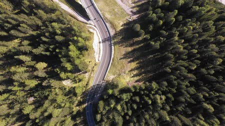 dolomitok : Aerial top view of mountain road through the wood - Aerial video of Dolomites in Italy with countryside road running through green trees - Travel and nature concepts