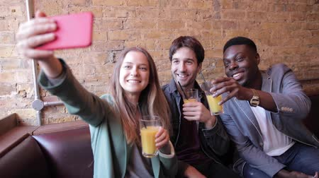 Happy friends having fun at bar and taking a selfie - Multiracial group enjoying time at pub restaurant drinking together - Funny people smiling and laughing, happy lifestyle