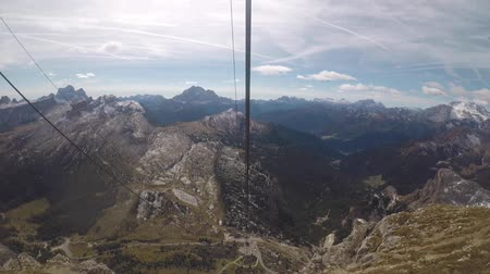 View from cable car ride on Dolomites mountains in Italy. Cable car between Passo Falzarego and Rifugio Lagazuoi, beautiful view of the mountains all around on a sunny day