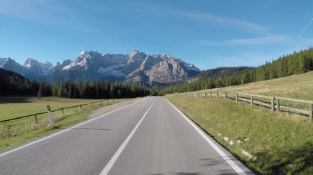 Driving on Italian alps with beautiful mountains on background. Empty road in Trentino, Italy, with green trees and meadows. Travel and transportation concepts 動画素材