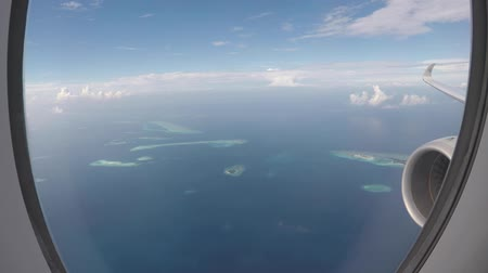 Airplane flying over atolls before landing in Maldives, over wing window view. Low altitude flying over beautiful sea water on final approach to the Male airport. Transportation and travel concepts