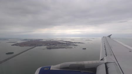 Airplane flying over Venice before landing, over wing window view. Low altitude flying on final approach to the airport. Transportation and travel concepts