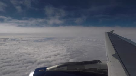 Airplane flying through clouds, over wing window view. Low altitude flying on final approach to the airport. Transportation and travel concepts