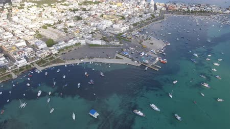 Beautiful tourist port aerial view with emerald water in southern Italy. Panoramic view of coastline with sails and boats at harbour on a sunny day. Travel and nature concepts.