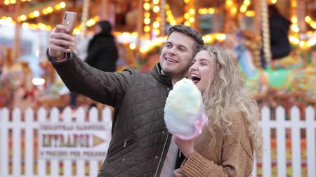 luna : Happy couple taking a selfie at amusement park and eating cotton candy - Young caucasian couple spending time together at funfair, talking and laughing with carousel on background - slow motion video Stock Footage
