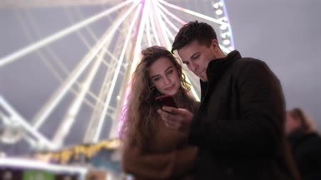 luna park : Happy couple having fun at amusement park and looking at mobile phone - Young caucasian couple spending time together at funfair, talking and laughing with ferris wheel on background - slow motion video