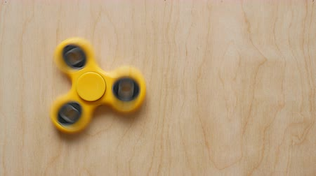 fidget spinner : Fidget spinner toy rotates on wooden background top view Stock Footage