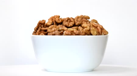 Walnuts in bowl rotating on white background Dostupné videozáznamy