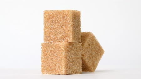 Cubes of brown sugar rotating on white background
