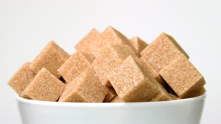 Cubes of brown cane sugar in bowl rotating close-up on white background Dostupné videozáznamy