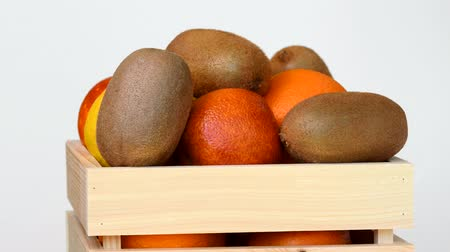 kivi : Fruits rotating in wooden box on white background Stok Video