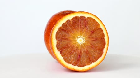 Half and whole blood orange rotating on white background Dostupné videozáznamy