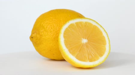Whole and half lemon rotating on white background