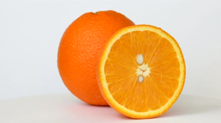 Whole and half orange rotating on white background