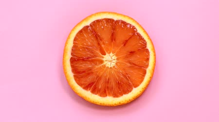 Blood orange slice rotating top view on pink background