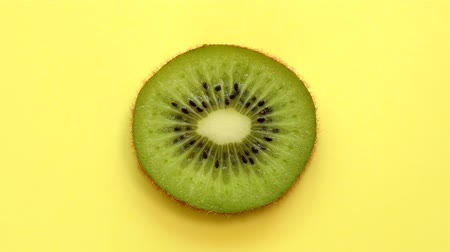 Slice of kiwifruit rotating top view on yellow background Dostupné videozáznamy