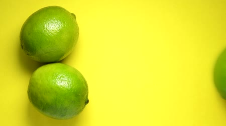 свежий : Lime rolling on yellow background top view Стоковые видеозаписи