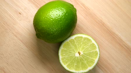 Whole lime and half rotating top view on wooden background Dostupné videozáznamy
