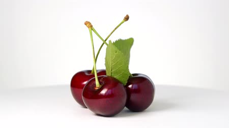 Ripe sweet cherry rotating on white background
