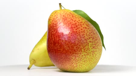 Whole pear and half rotating on white background