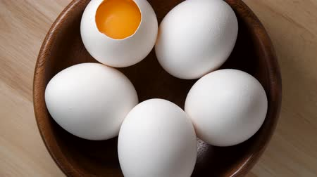 White chicken eggs rotating in wooden bowl top view