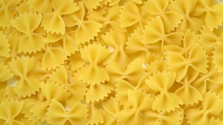 Uncooked farfalle or bow-tie pasta rotating top view