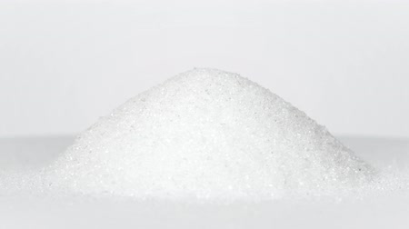 Pile of white sugar rotating on white background