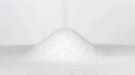 Sugar pouring onto white table