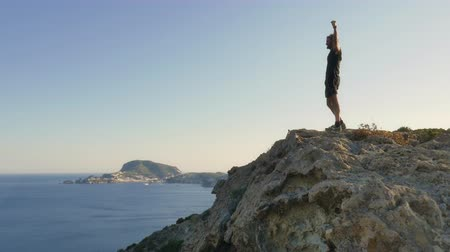 путешествие : Runner exulting on top of a cliff on an island in front of the ocean Стоковые видеозаписи
