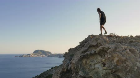 cliff : Running man arrives on top of a cliff on an island in front of the ocean