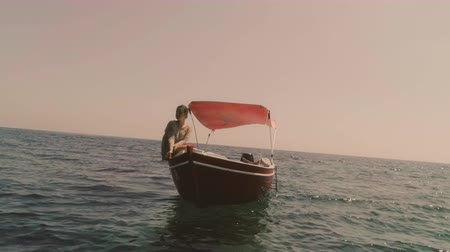 looking far away : Young woman on a red boat in the middle of the ocean