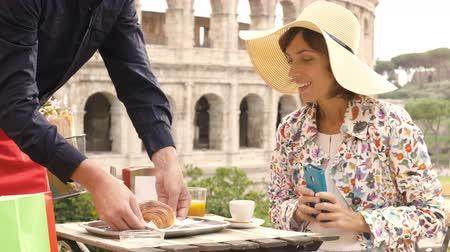 roma : Beautiful young woman tourist with smartphone sitting at the table outside a bar restaurant in front of the Colosseum in Rome gets coffee, juice and cornetto from the waiter. Elegant dress with large hat and colorful shopping bags. Stok Video
