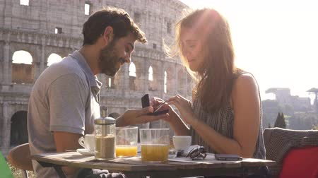 casamento : Happy couple marriage proposal with ring sitting at restaurant in front of colosseum in rome at sunset emotional