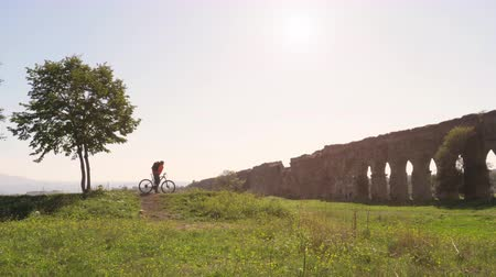 roma : Cyclist with bike reads map for direction in front of ancient roman aqueduct in a park. Young attractive athletic man with orange sportswear and backpack in parco degli acquedotti in Rome under a tree on a hill at sunset Stok Video