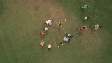 kamp : Top view kids in summer camp playing in green grass field slow motion aerial